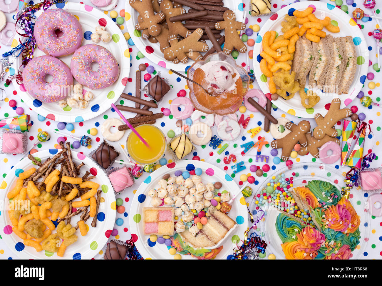 Childrens party food including sandwiches, cake, jelly and ice cream, biscuits, crisps, sweets and doughnuts on - Stock Image