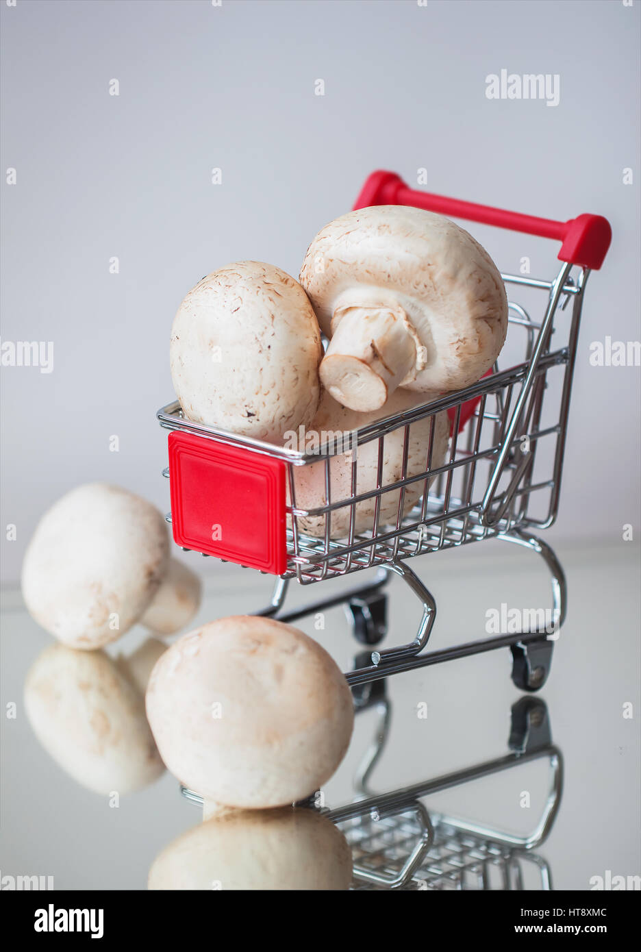Mini cart shopping witch organic mushrooms on light background. Diet, health or vegetarian food concept. - Stock Image