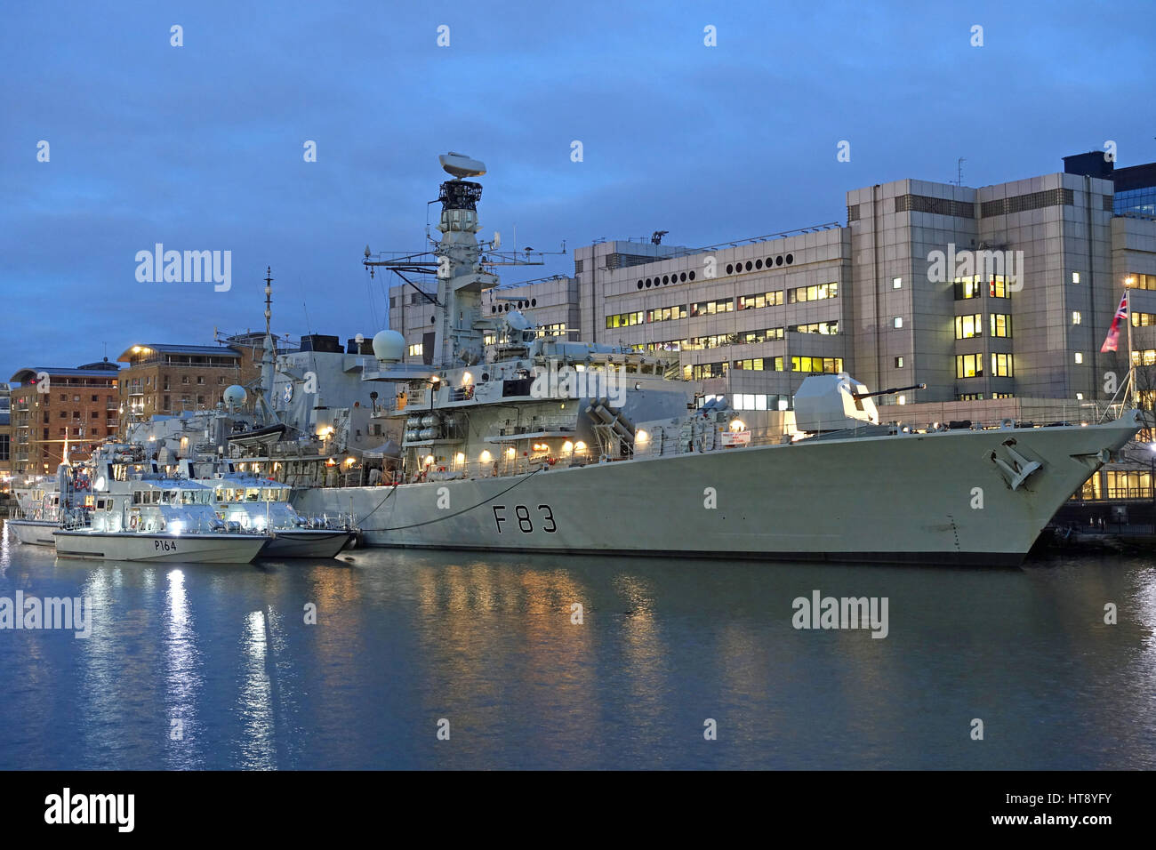 View of the Type 23 frigate HMS St Albans of the UK Royal Navy moored alongside at West India docks at night during - Stock Image