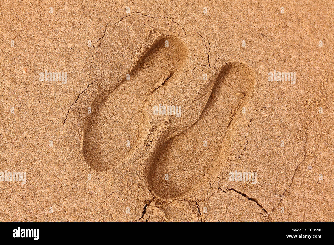 Footprint, sole of a shoe on the sand - Stock Image