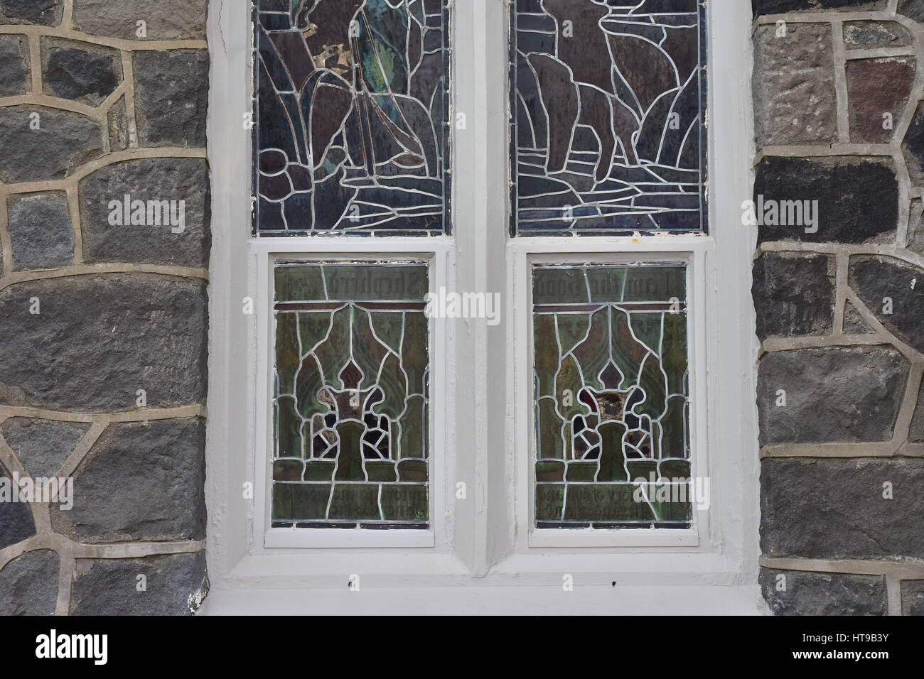 Detail of stained glass window panes in white wooden frame on stone ...