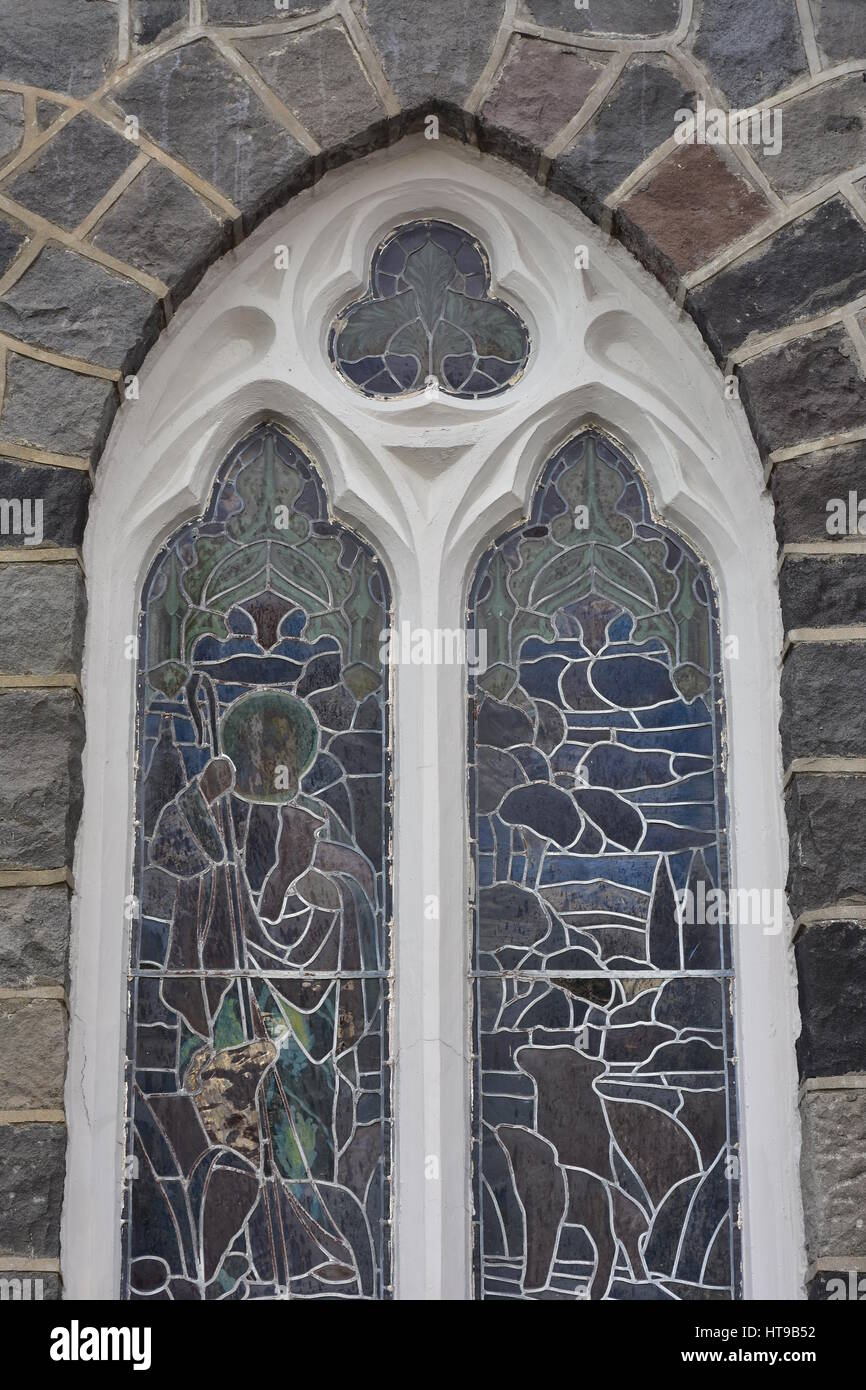 Arched stained glass window with white wooden frame on stone church ...