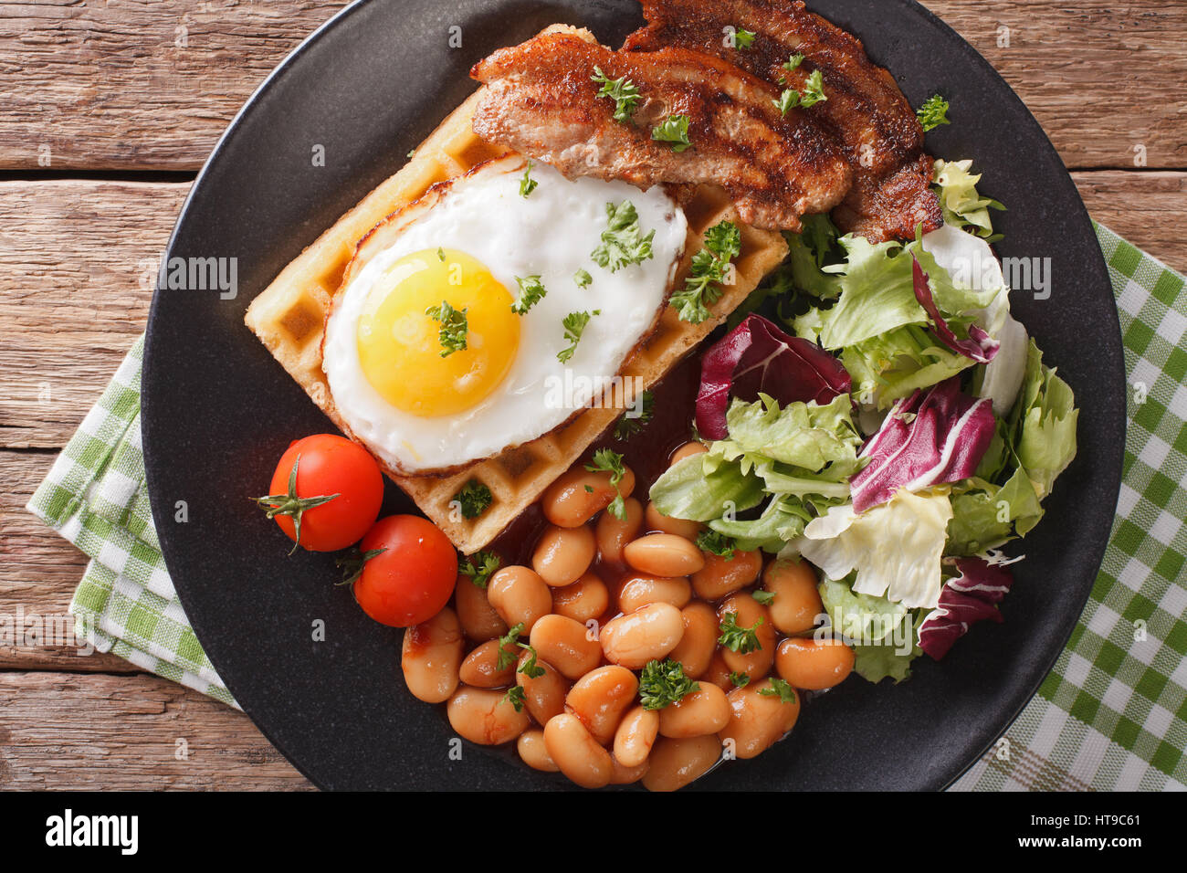 hearty breakfast with fried egg, waffles, bacon, mix salad and beans close-up on the table. horizontal view from - Stock Image