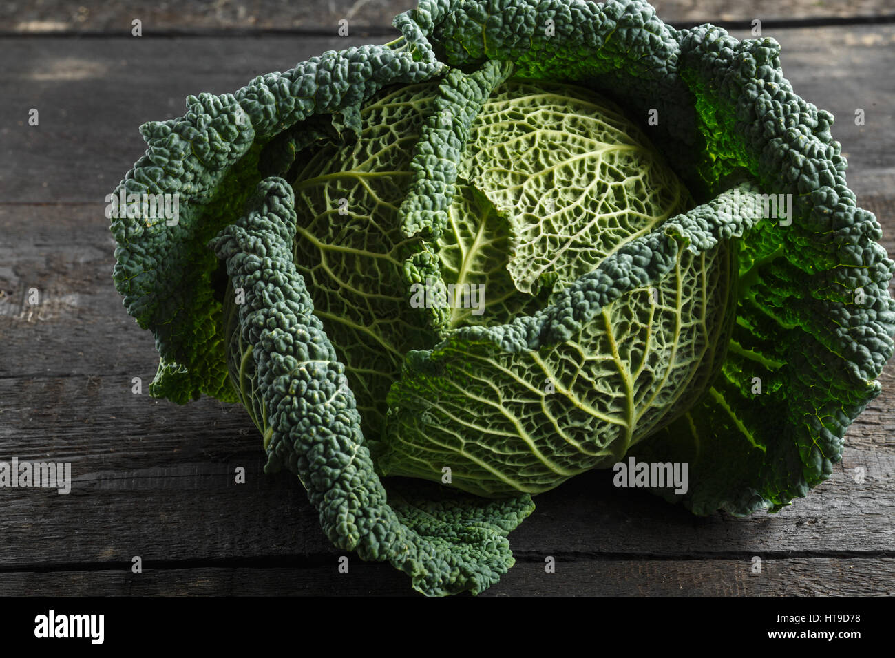 Savoy cabbage on a background of a dark wooden table. - Stock Image