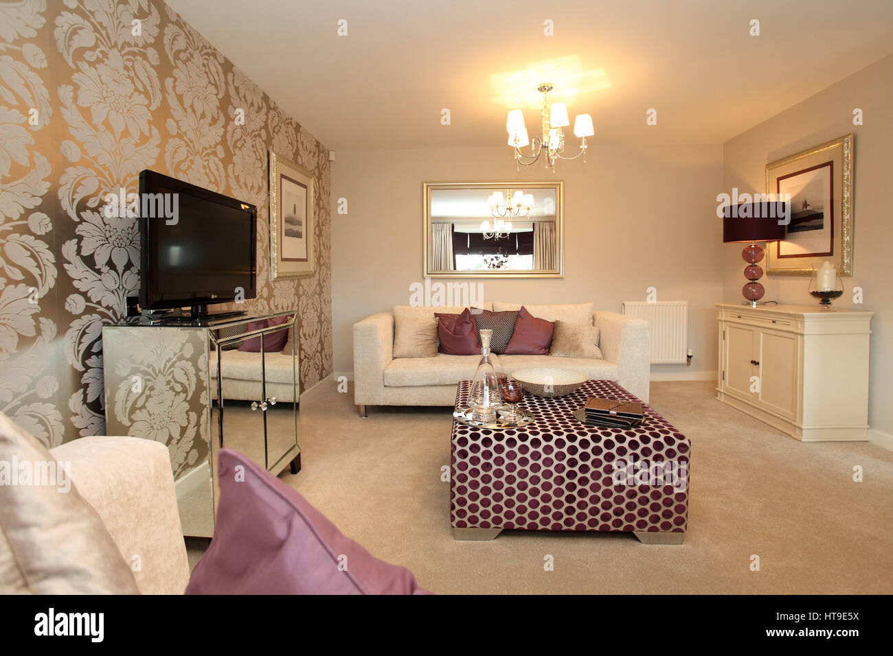 Home interior. Living room, lounge, decorated in pink and cream colours, silver reflective wallpaper with leaf pattern - Stock Image