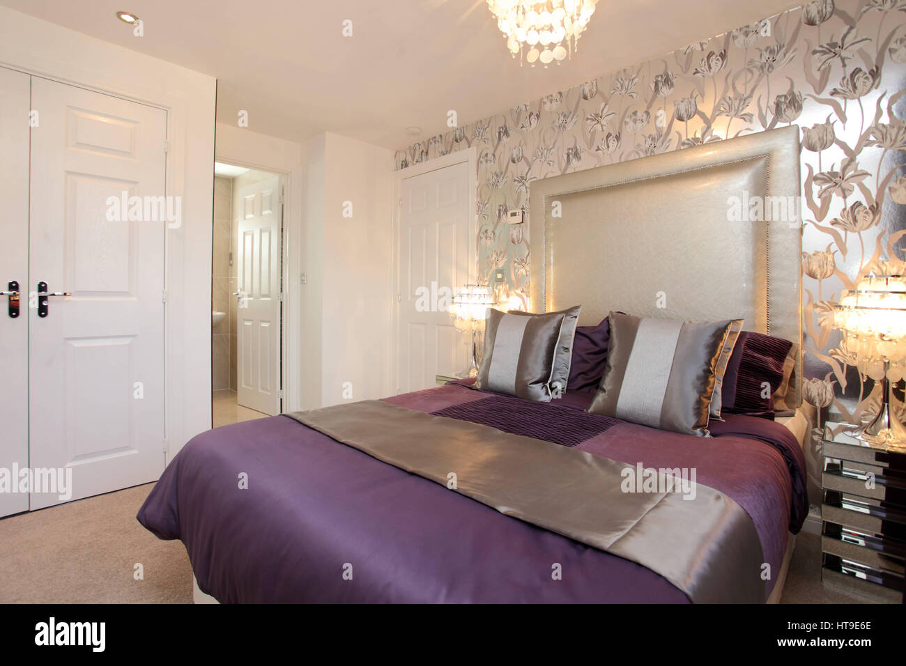 Home interior, bedroom decorated in mauve and silver, feature wall, silver wallpaper,flower pattern, en suite, wardrobes - Stock Image