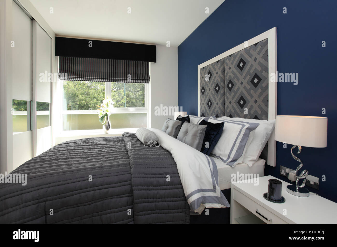 Home interior, bedroom, blue, decor, bed spread, padded headboard, feature wall, chair, grey, - Stock Image