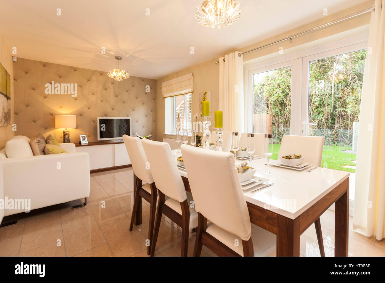 Home interior. dining room, french windows, sliding doors, neutral colours, cream, white, beige,dining table laid,eating, - Stock Image
