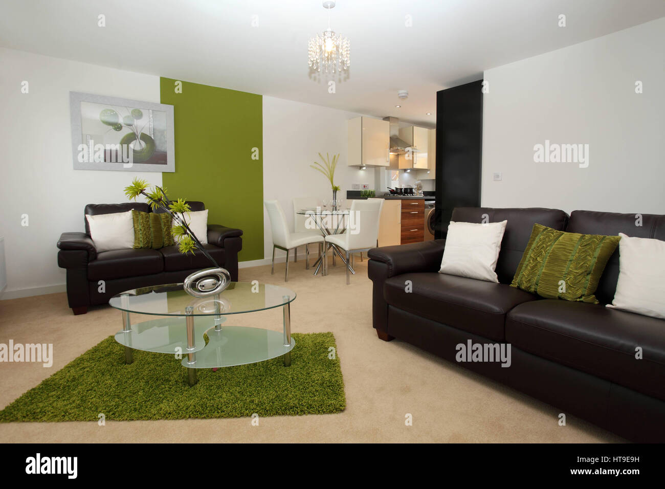 Apartment interior, modern lounge/kitchen/diner, living room, space, dining area, green rug, glass coffee table, - Stock Image