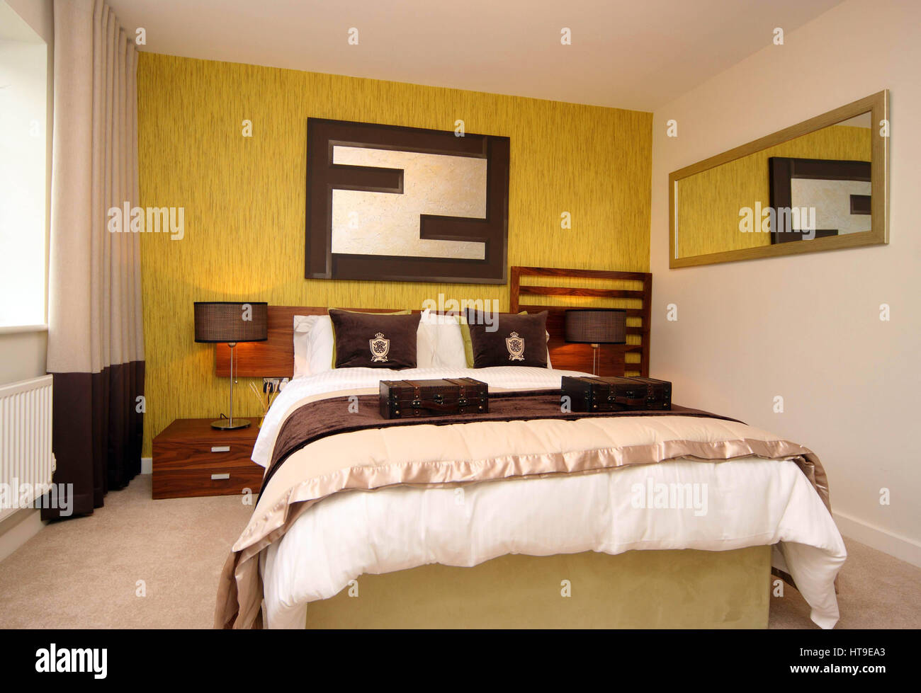 Home interior, bedroom, feature wall, green, yellow, mirror, bedside tables, lamps, cushions, - Stock Image