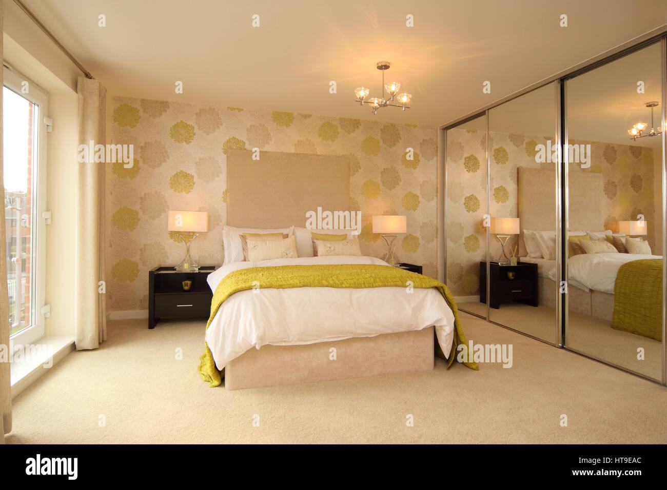 Home interior, modern bedroom, spacious, mirrored wardrobe, yellow cream decor, lamps, bedspread, throw, cushions, - Stock Image