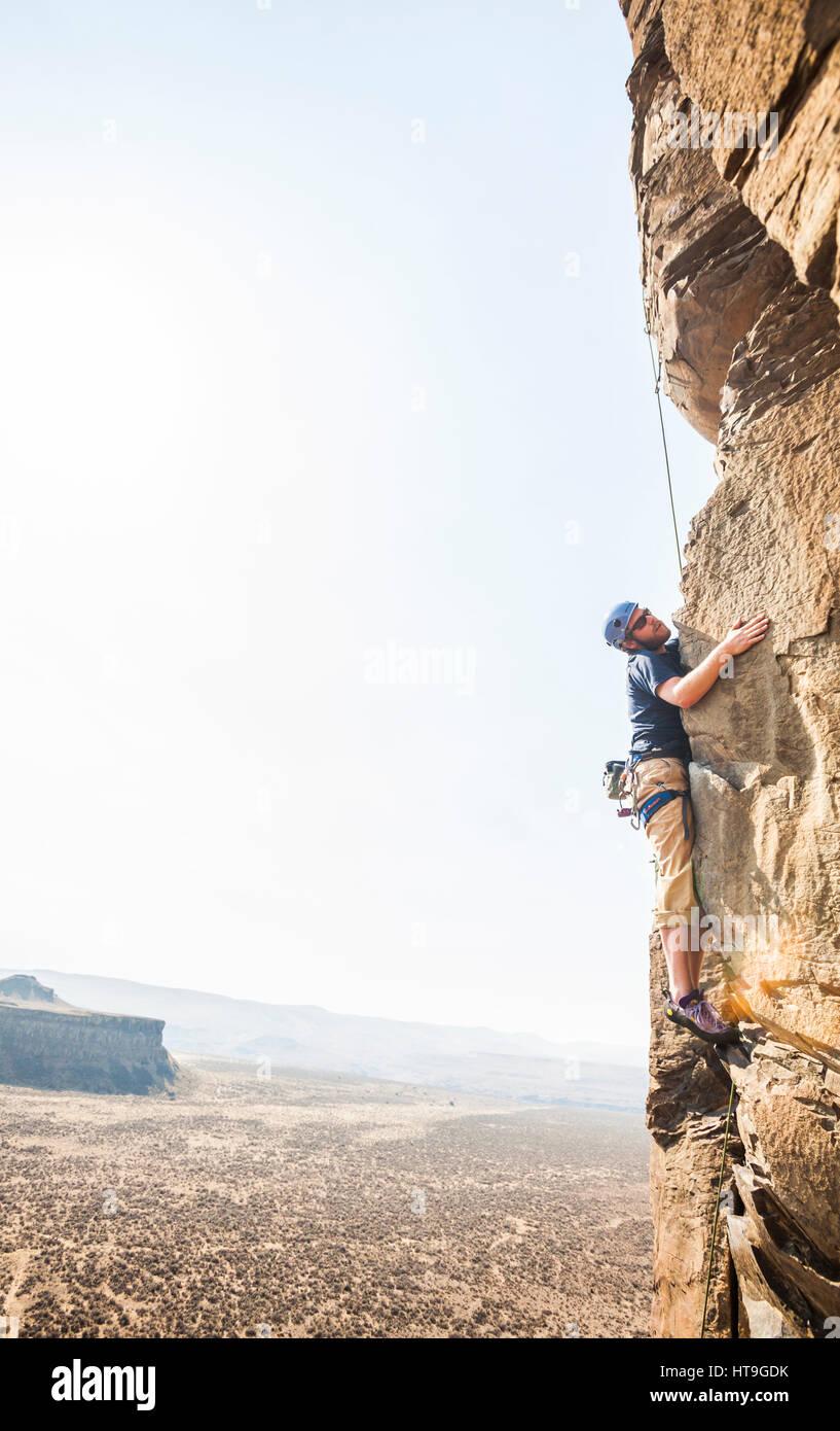 A man rock climbing in Echo Basin at the Vantage climbing area in Eastern Washington, USA. - Stock Image