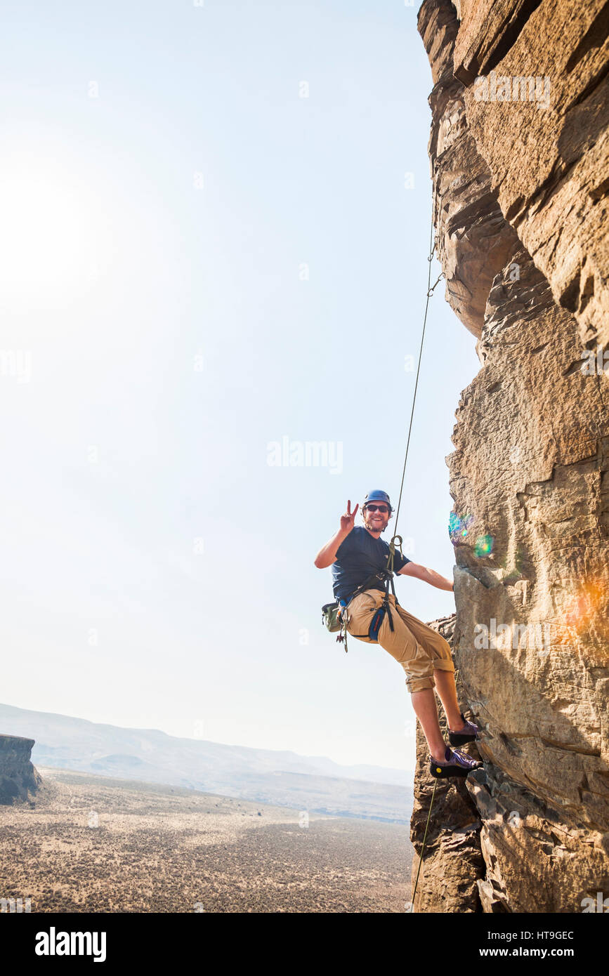 A man flashing a peace sign while rock climbing in Echo Basin at the Vantage climbing area in Eastern Washington, - Stock Image