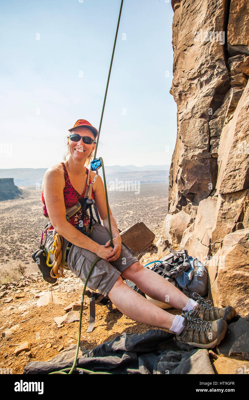 A mid 40's aged woman rock climbing in Eastern Washington. - Stock Image