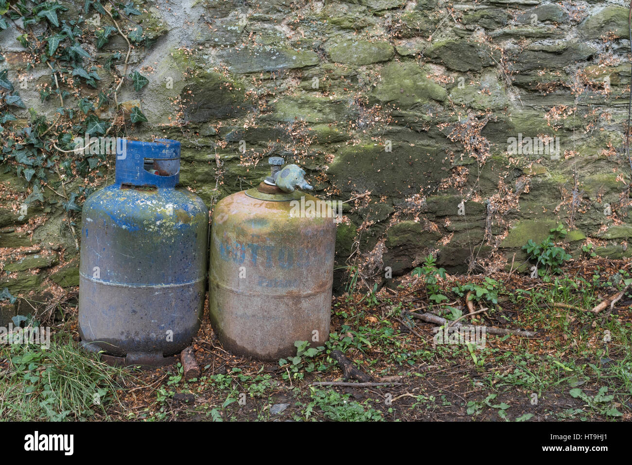 Old propane and butane bottle - empty, out in the open, and long forgotten. - Stock Image