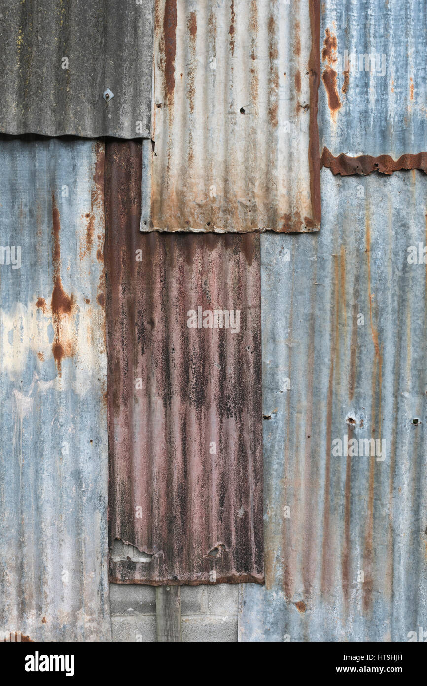 Overlaid sections of rusting galvanised / galvanized steel sheet. Weathered metal texture. - Stock Image