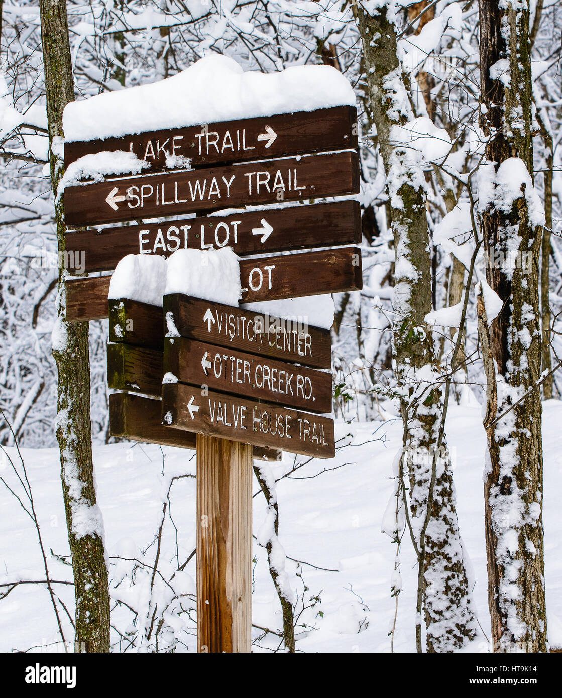 A trail sign at Radnor Lake State Natural Area in Nashville, Tennessee covered by snow. - Stock Image