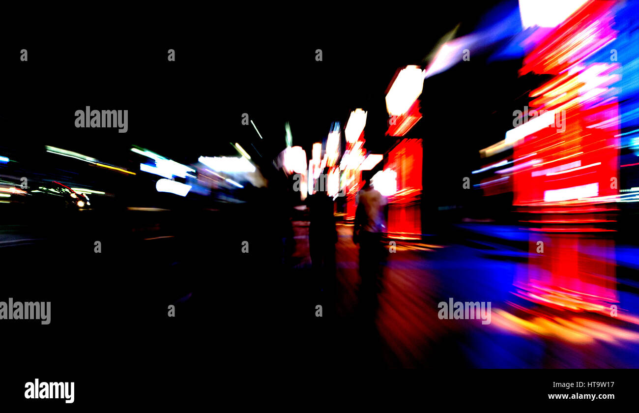 People walking on street with motion, blur and zoom effects. Negative space. - Stock Image