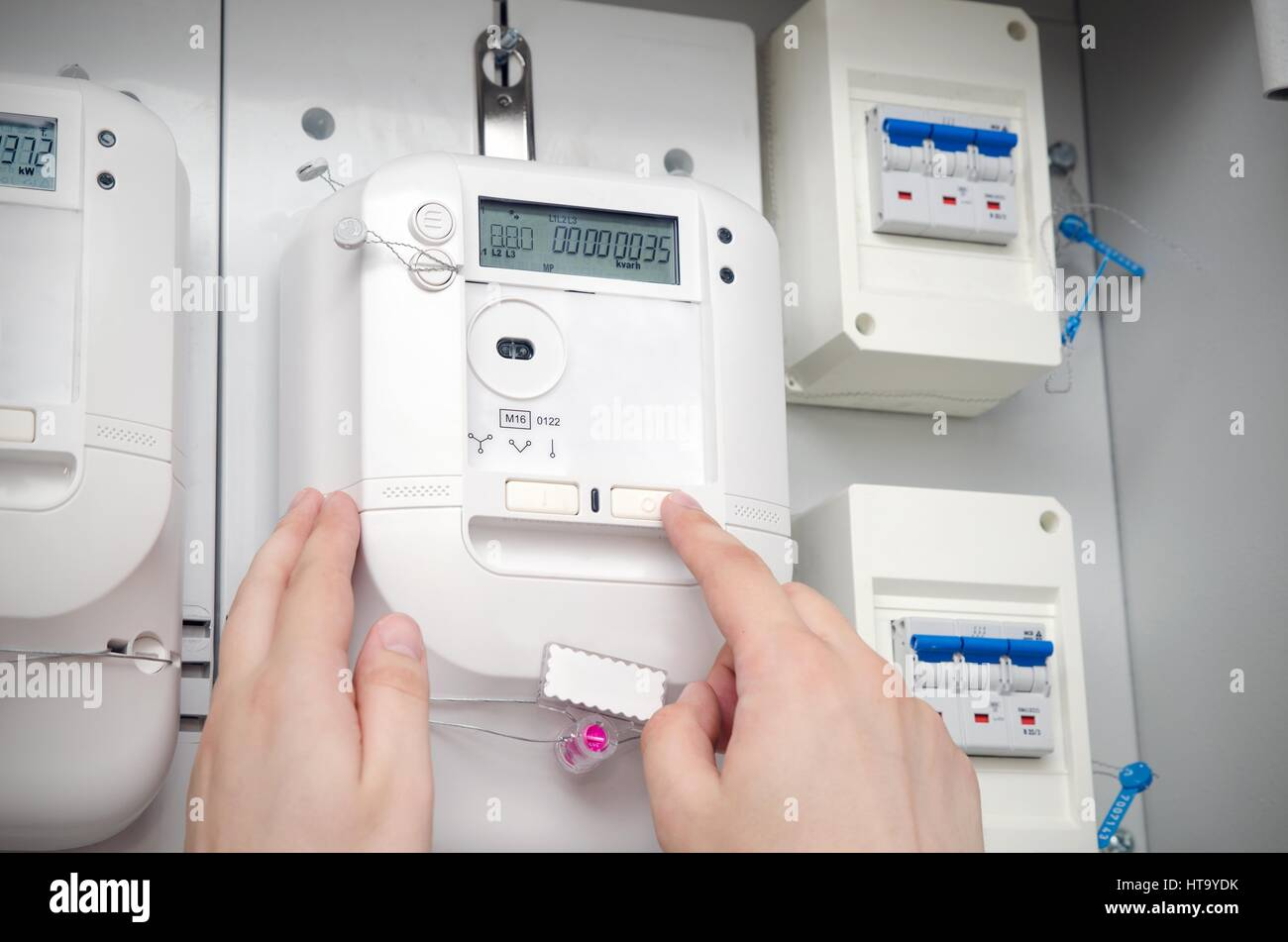 Electric energy meter. Electrical technician servicing unit - Stock Image