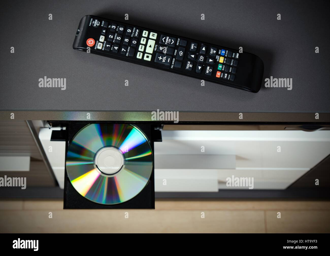 Remote control and Blu-ray or DVD player with inserted disc. - Stock Image