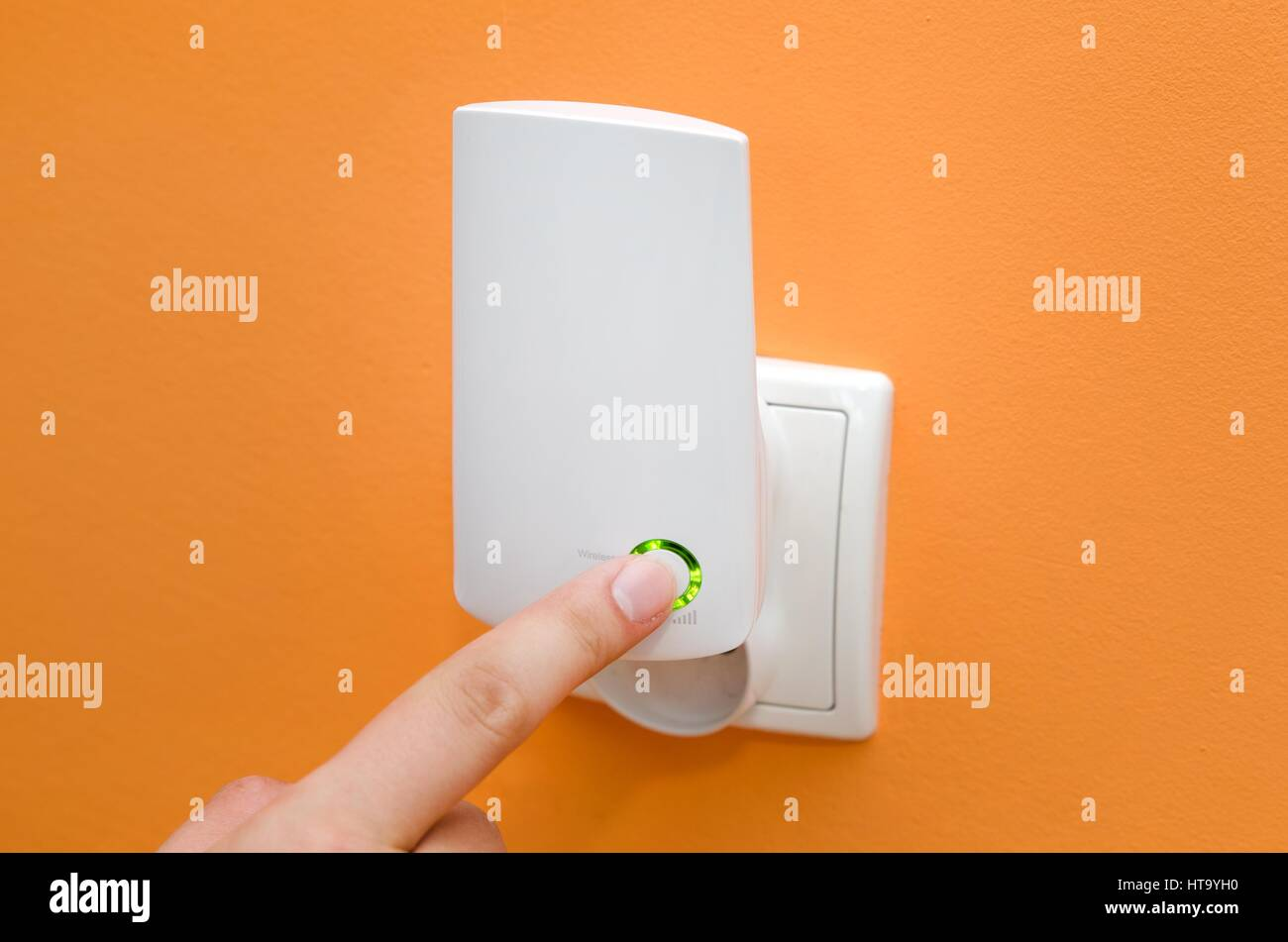 WiFi repeater in electrical socket on orange wall. Simply way to extend wireless network in home - Stock Image