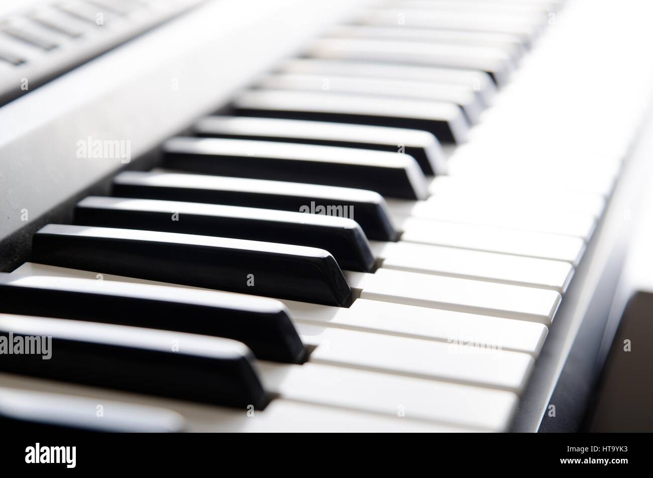 Piano keys of electronic keyboard instrument. Close up photo - Stock Image