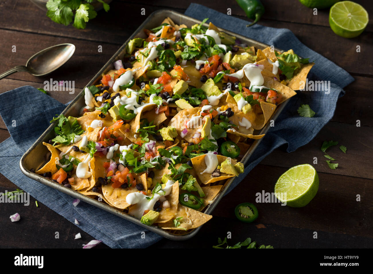 Homemade Loaded Sheet Pan Nachos with Cilantro Lime Tomato and Onion - Stock Image