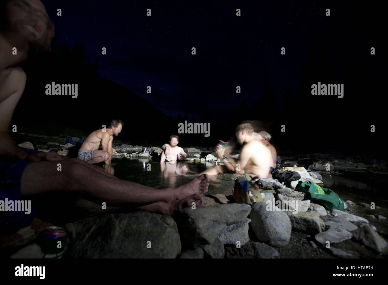 July 30, 2013 - Idaho, USA - Nighttime hot spring session.A large group of friends take rafts, kayaks and duckies - Stock Image