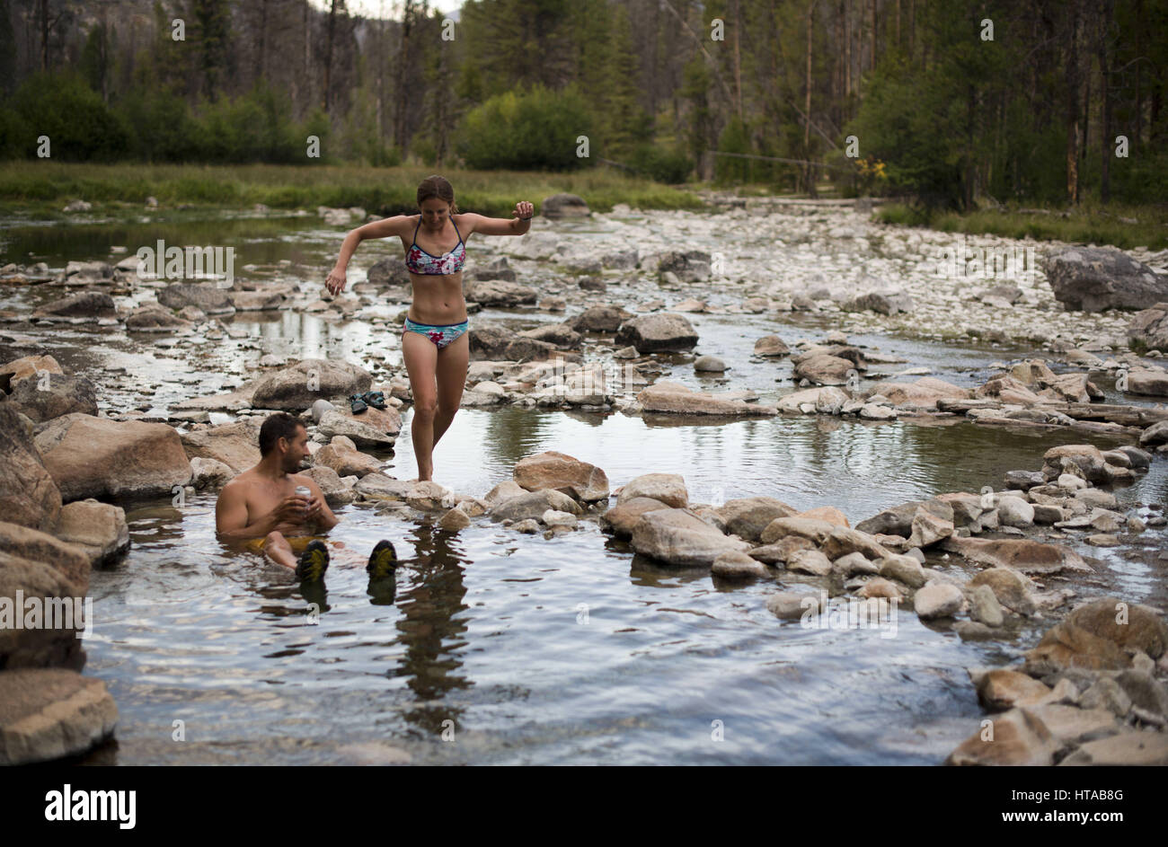 July 30, 2013 - Idaho, USA - Hot spring session with bikini and board shorts.A large group of friends take rafts, - Stock Image