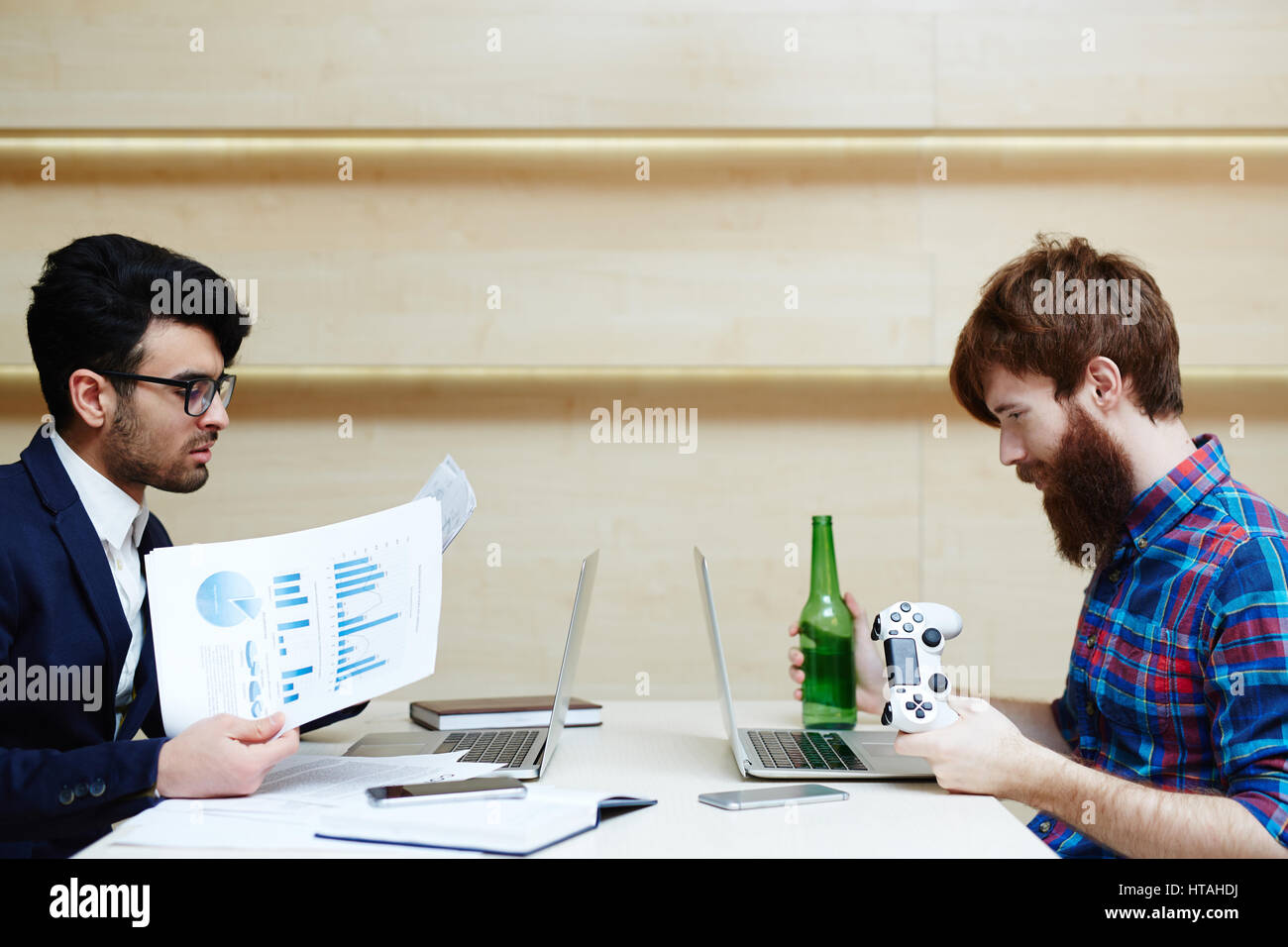 Profile view of hard-working businessman in white shirt and suit analyzing financial documents while his lazy bearded - Stock Image