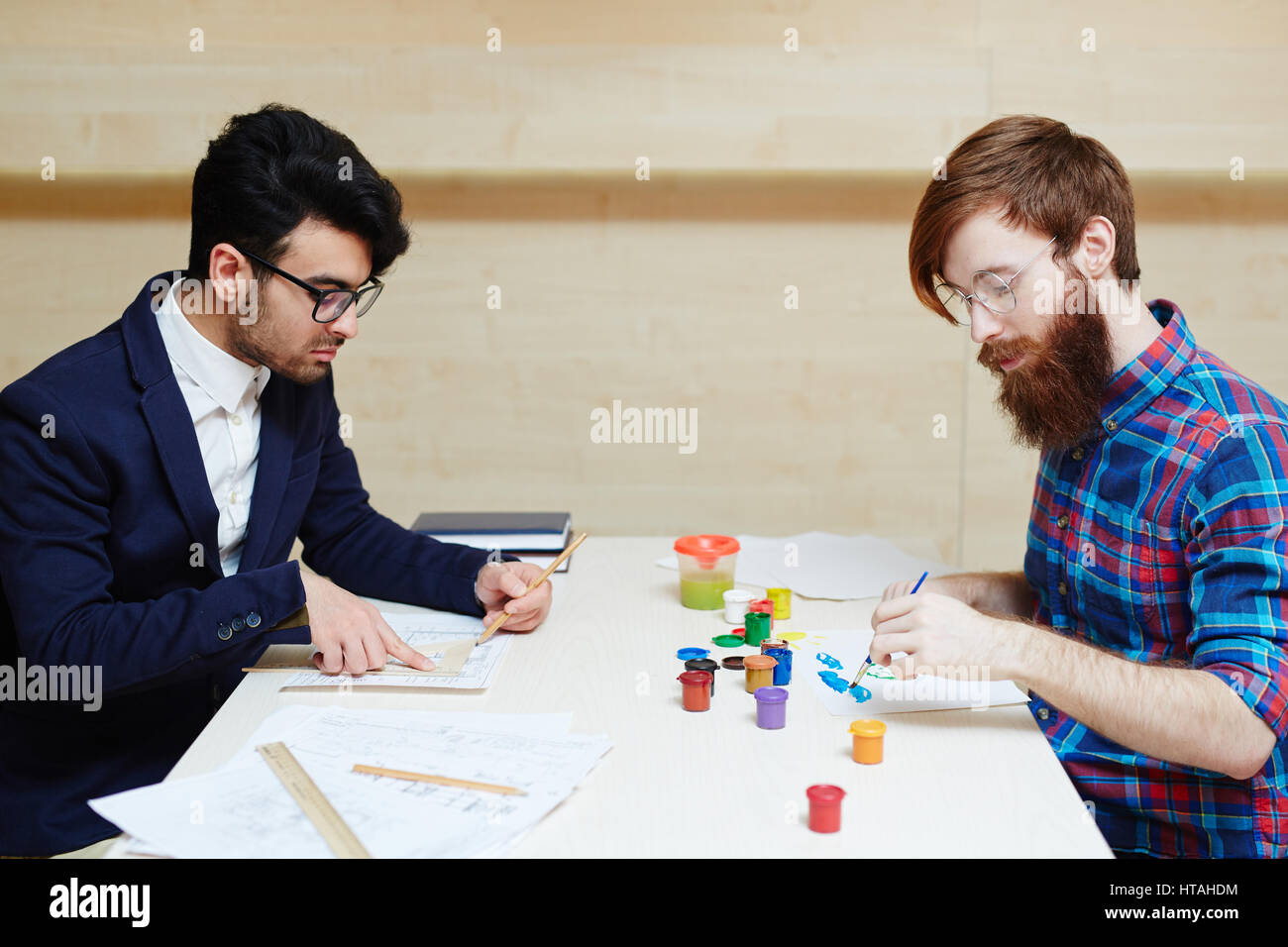 Young bearded worker in formalwear sitting at desk and drawing architecture project with pencil and ruler while - Stock Image