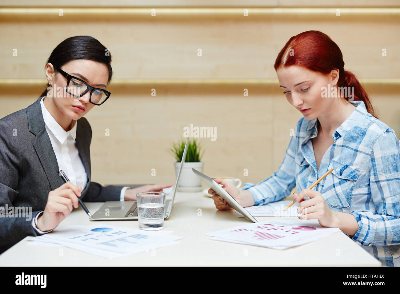 Concentrated pretty businesswoman in eyeglasses and formalwear examining documents and making notes while her red - Stock Image