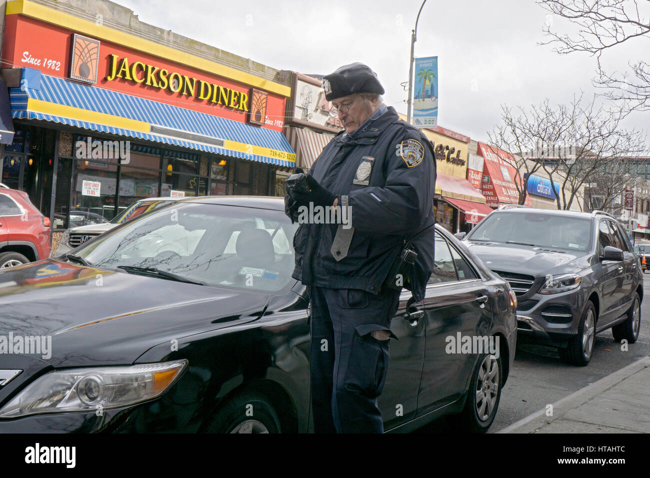 A New York City traffic policeman writing a summons for a car with a parking violation on 74th Street in Jackson - Stock Image