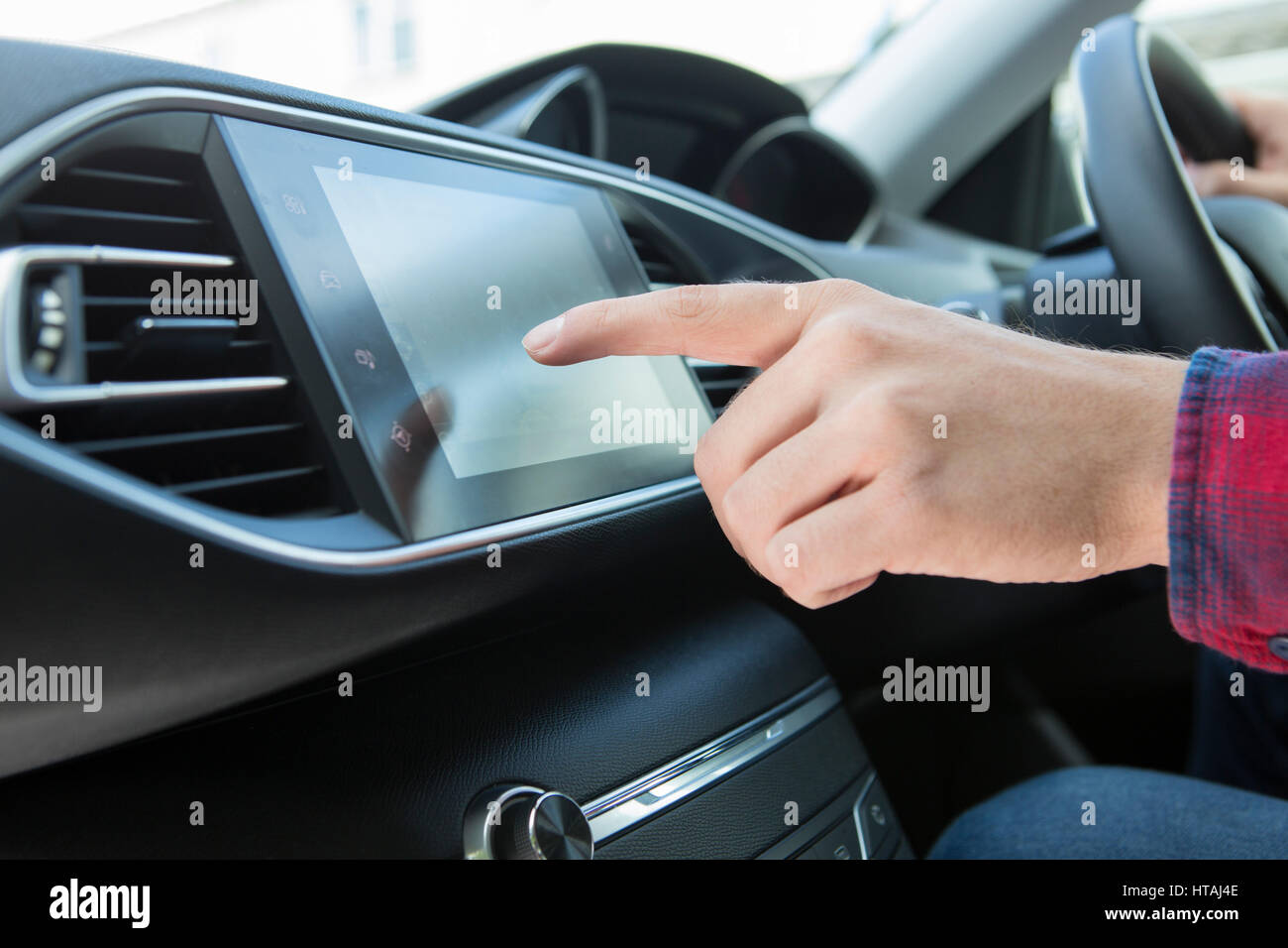 Close Up Of Driver Using Touchscreen In Car - Stock Image