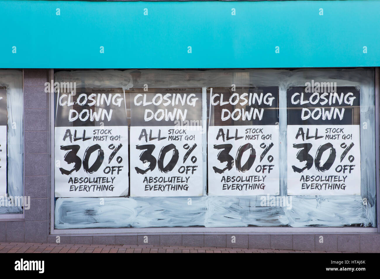 Exterior Of Shop With Closing Down Notice In Window - Stock Image