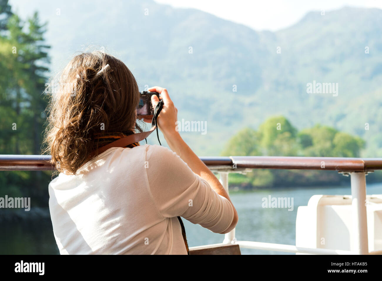 Unrecognisable young female enjoying boat ride, taking photographs, Loch Katrine, Scottish Highlands, UK Stock Photo
