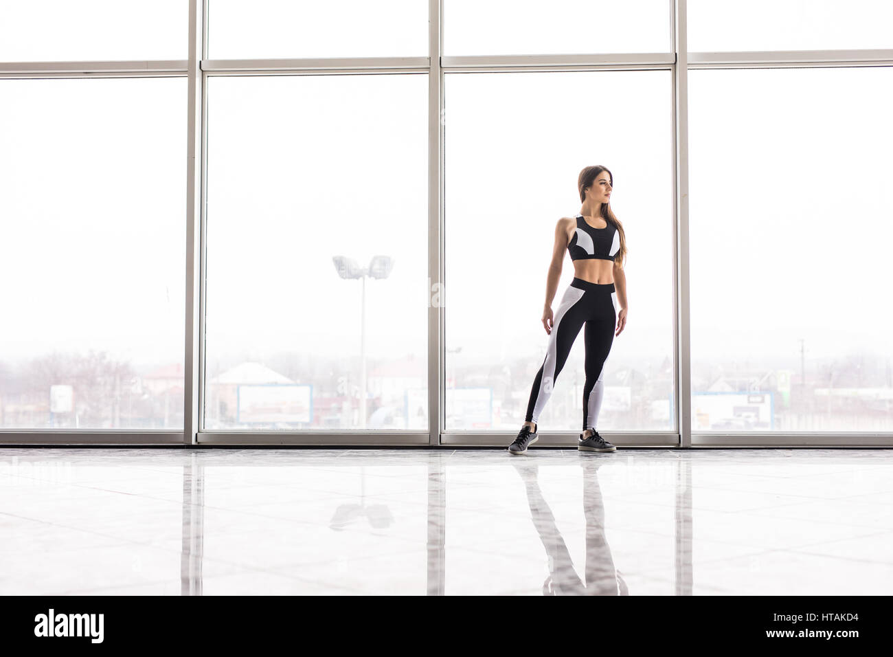 Silhouette of sporty girl before training against panoramic windows Stock Photo