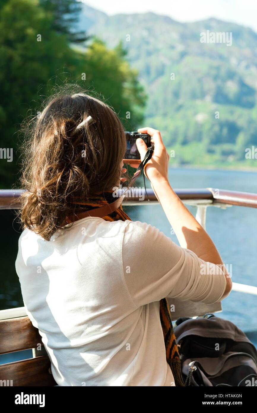 Unrecognisable young female enjoying boat ride, taking photographs, Loch Katrine, Scottish Highlands, UK - Stock Image