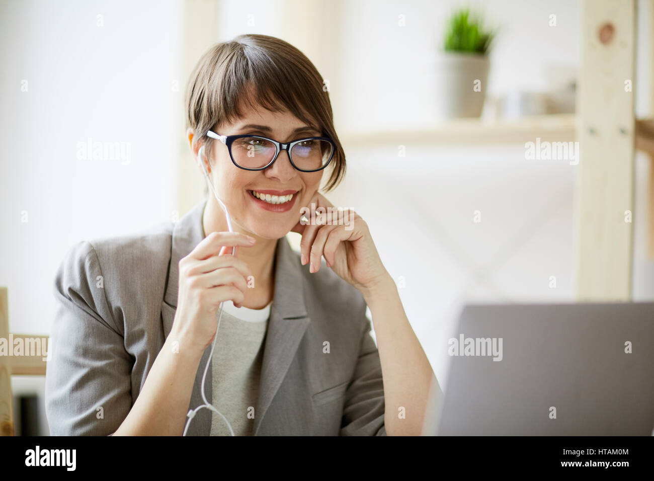 Portrait of young successful businesswoman wearing creative haircut and glasses smiling cheerfully while holding - Stock Image