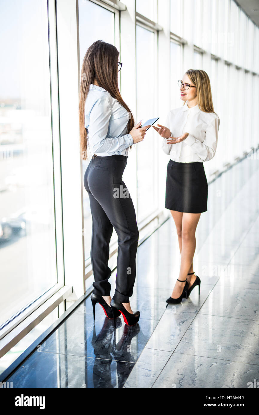 Businesswomen Having Informal Meeting In Modern Office with panoramic windows. Office concept - Stock Image