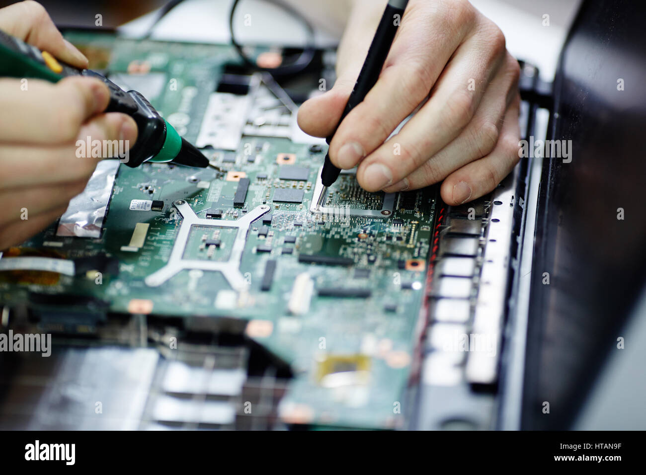 Laptop Main Components Stock Photos Testing Circuit Board Closeup Shot Of Male Hands Electric Current In Disassembled Using Multimeter