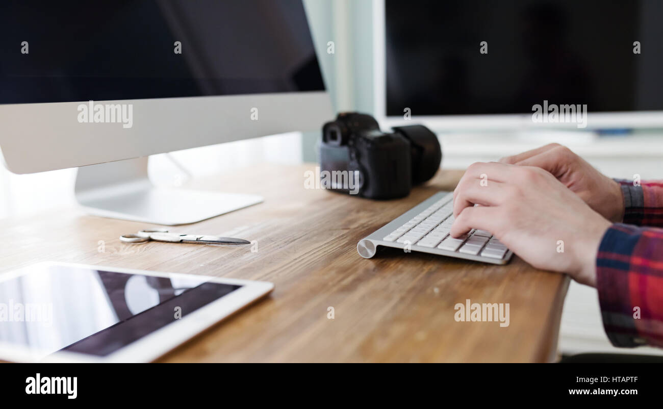 Photographer retoucher working on photos and editing on desktop - Stock Image