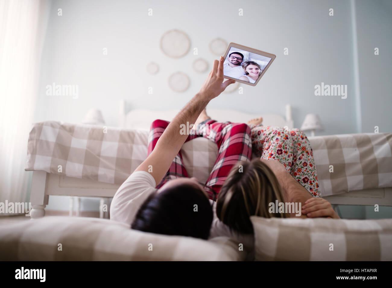 Loving couple taking selfies at home in pajamas - Stock Image