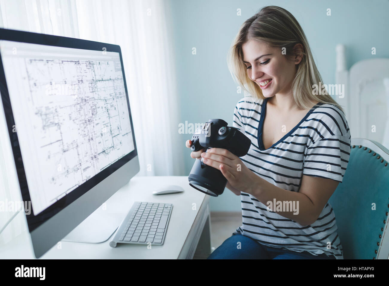 Designer and photographer woman looking at dslr camera - Stock Image