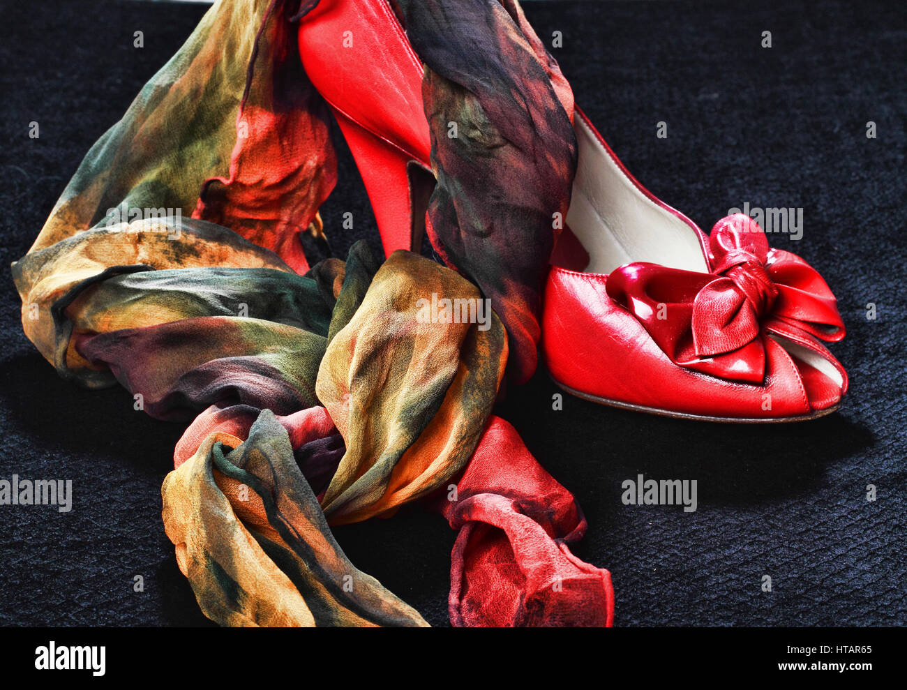 a red shoe with a bow in front, on top and in front of it, a silk scarf in yellow,green,orange,red and yellow. Placed - Stock Image