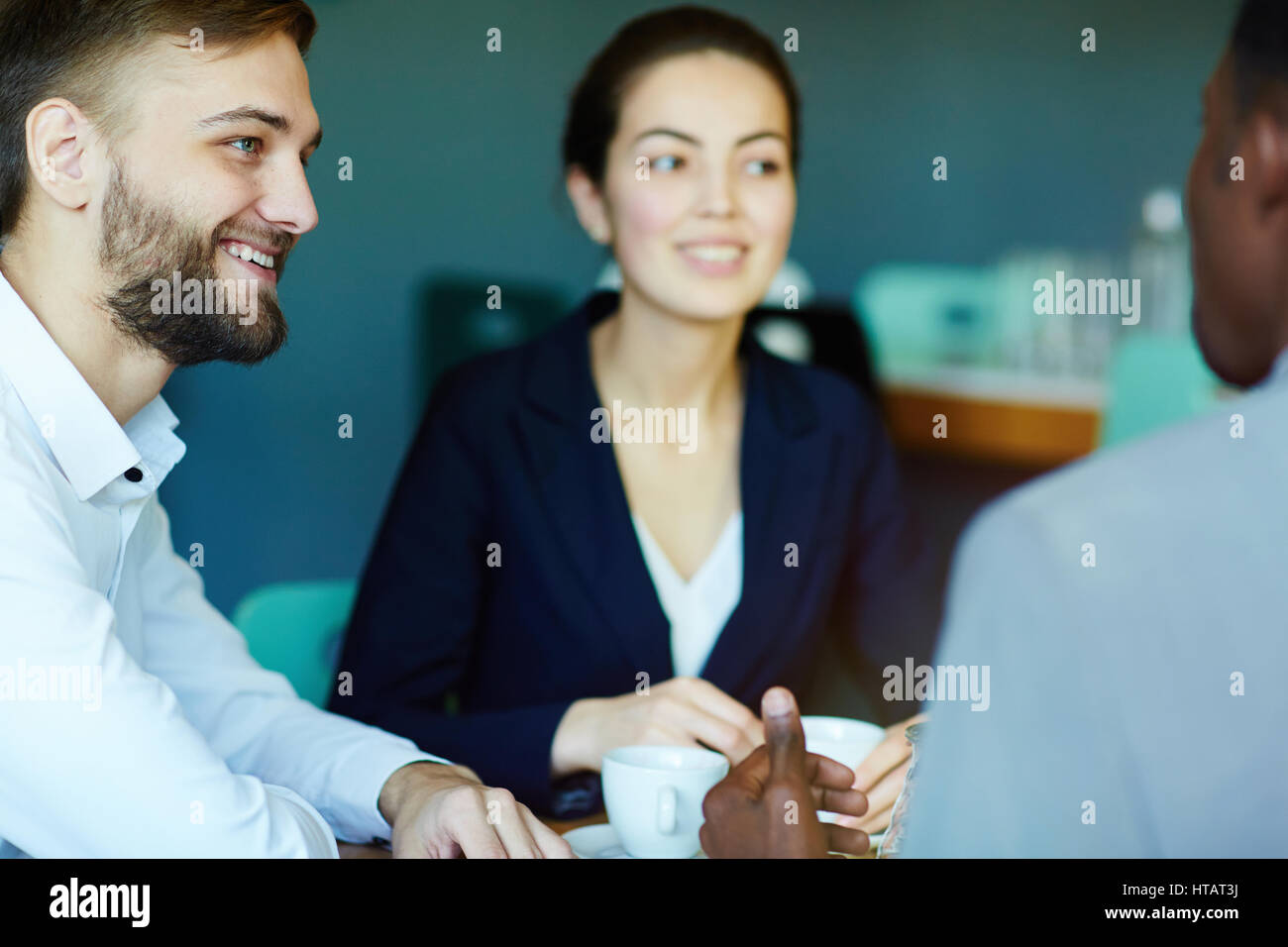 Businessman listening to co-worker at meeting - Stock Image