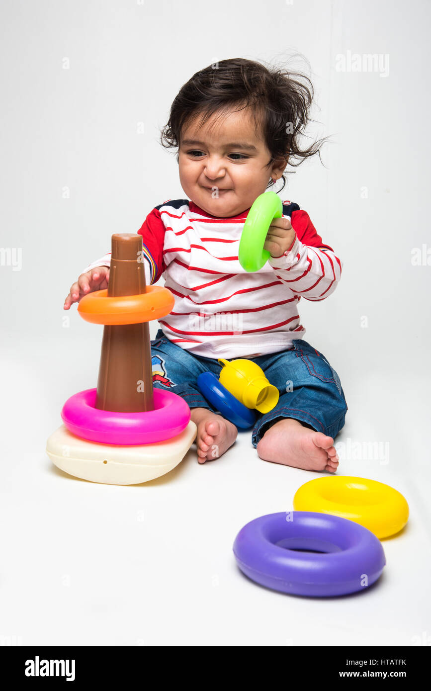 Indian baby boy playing over over white background and looking at camera - Stock Image