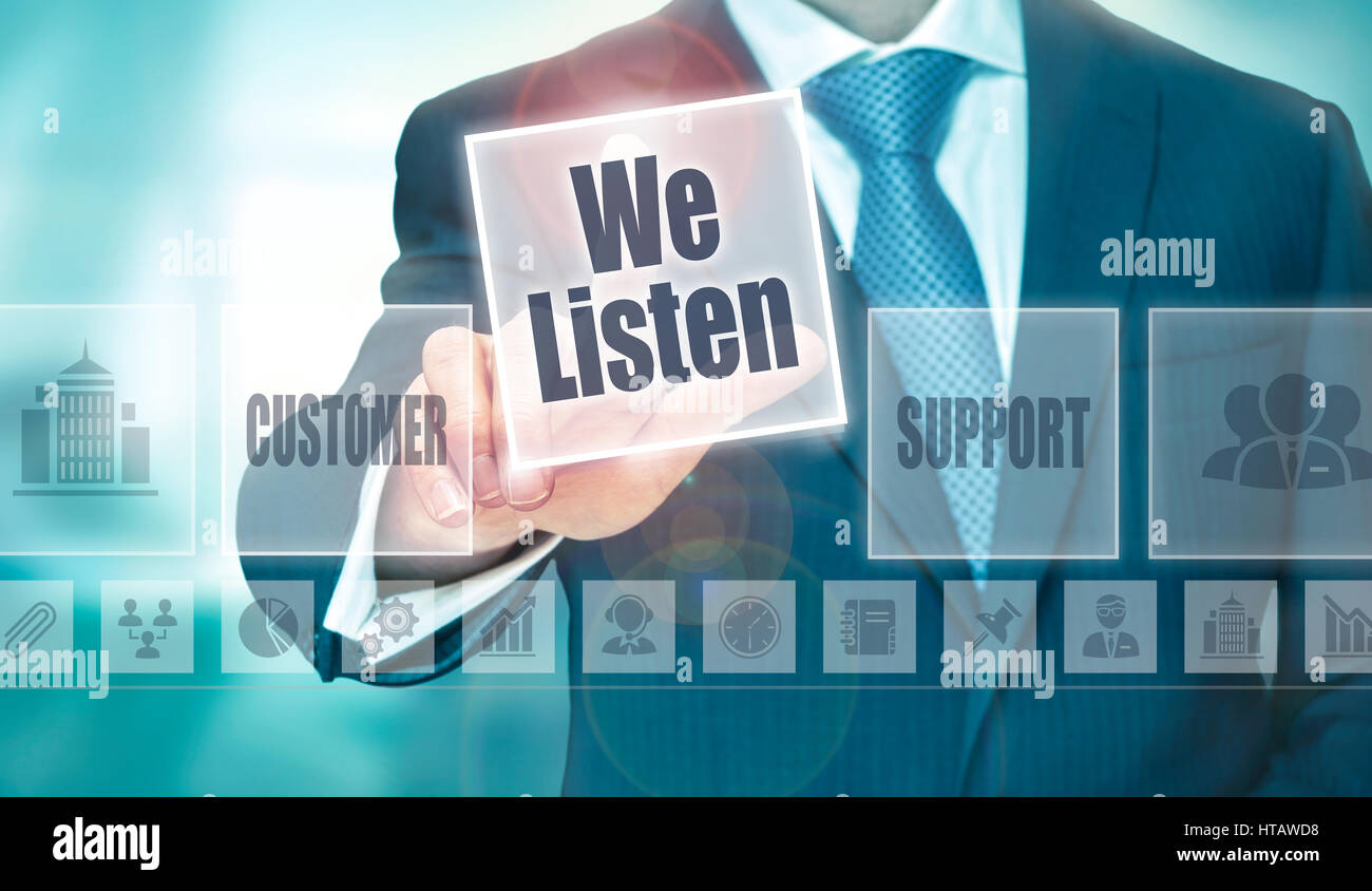 A businessman selecting a We Listen Concept button on a clear screen. - Stock Image