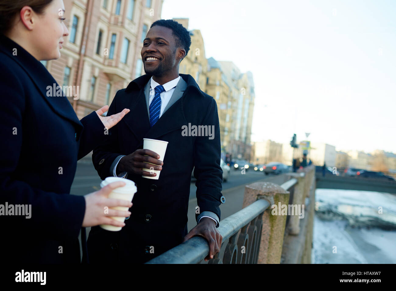 Portrait of two business colleagues in street of city by river talking to each other while holding disposable coffee Stock Photo