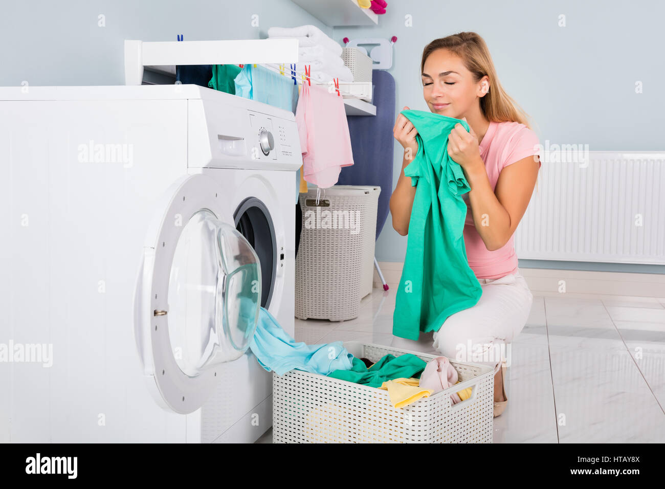 Young Smiling Woman Smelling Clothes After Washing In Washing Machine At Utility Room - Stock Image